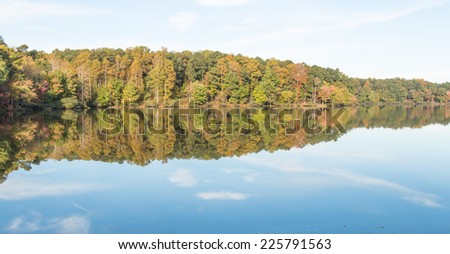 Fall foliage sky and clouds reflected on lake - stock photo