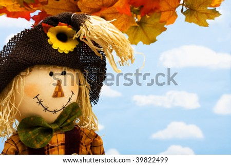 Fall leaves with a scarecrow making a border on a sky background, fall border - stock photo