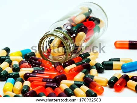 Fall out capsules around the glass - stock photo