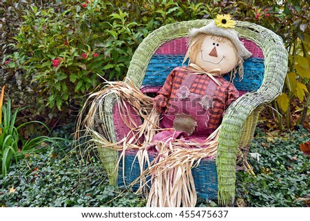 fall scarecrow sitting in a wicker chair in garden - stock photo