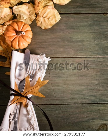 Fall Still Life Table Place setting with mini pumpkin, leaf and fork, knife, spoon on green, faux painted rustic wood board background, room or space for copy, text, your words.  Vertical grunge tone  - stock photo