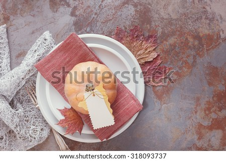 Fall table with pumpkin. White plates decorated with pumpkin, autumn leaves and placard. Thanksgiving Table Decorations - stock photo