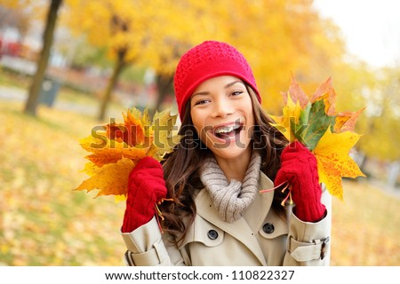 Fall woman happy and bliss in autumn city forest park holding colorful fall leaves smiling happy and joyful wearing tuque and knit gloves. Pretty multiracial Asian and Caucasian girl model. - stock photo