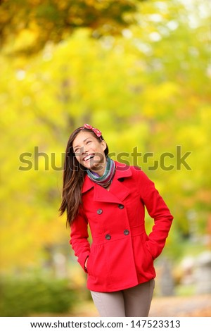 Fall woman walking amongst autumn trees. Beautfiul laughing young woman in a trendy red jacket walking amongst colourful yellow autumn trees with copy space. Mixed race Chinese Asian / Caucasian girl. - stock photo