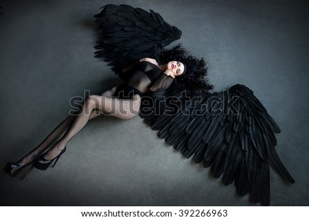 Fallen black angel with wings. Sexual woman - stock photo