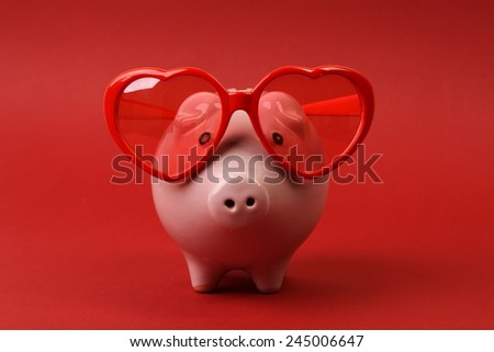 Fallen in love piggy bank with red heart sunglasses standing on red background - stock photo