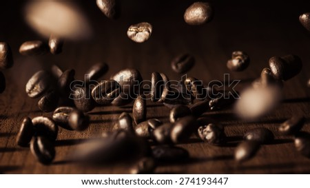 Falling coffee beans on a wooden table - stock photo