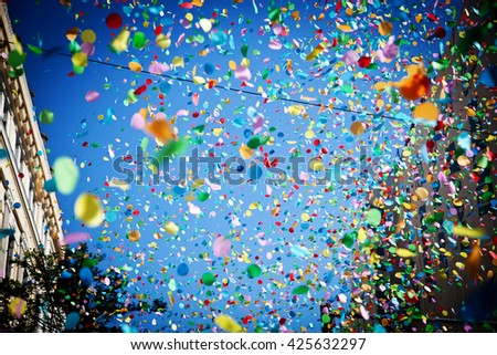 falling confetti in the city festival on blue sky background - stock photo