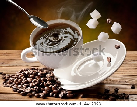 Falling  cup coffee, spoon and sugar cubes are falling down also. - stock photo