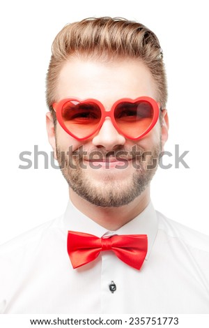 Falling in love. Close up portrait of Funny handsome smiling man isolated on white background wearing heart shaped sunglasses. - stock photo