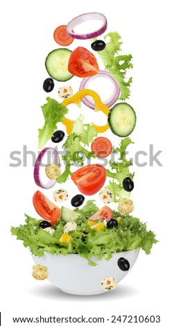 Falling ingredients for green salad in bowl with lettuce, tomatoes, Feta cheese, onion, olives and cucumber - stock photo