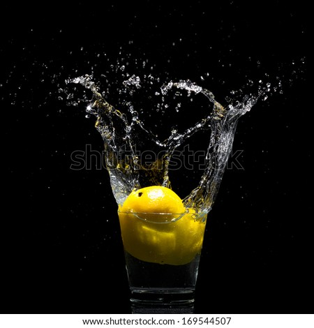 Falling lemon to glass with water - stock photo