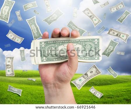 falling money on landscape - stock photo