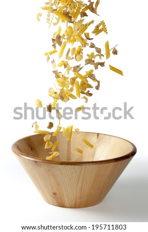 Falling pieces of pasta in a wooden bowl - stock photo
