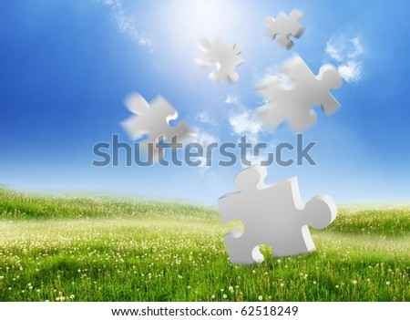 falling puzzle pieces on a green landscape - stock photo