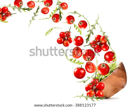 Falling salad in a wooden salad bowl. Tomato and basil isolated on white background - stock photo