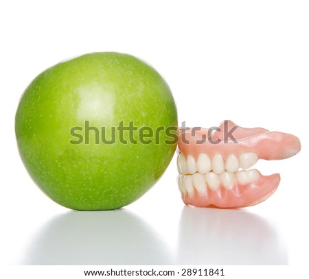 False teeth denture against green granny smith apple - stock photo