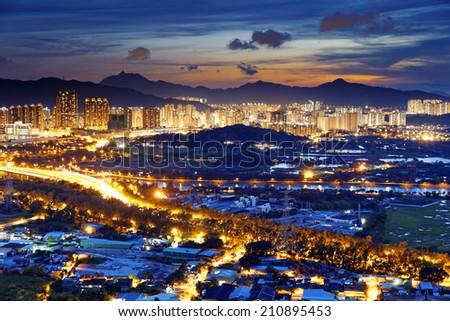Famed skyline of Hong Kong  Yuen Long downtown sunset - stock photo