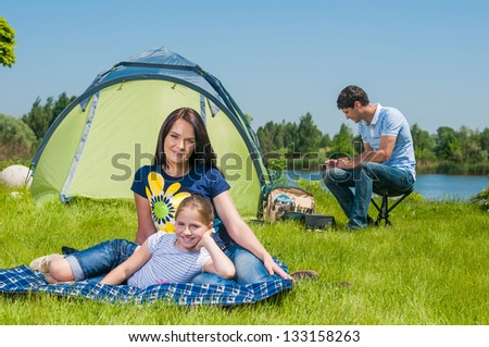 Families resting on the grass and camping with tent - stock photo