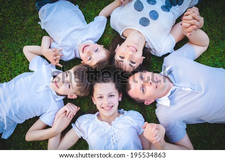 families with children lying on the grass - stock photo