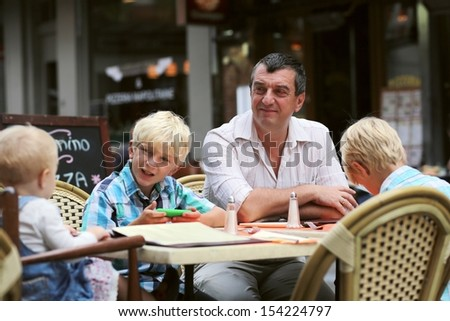 Family, a father with three children, two teenager twin sons and daughter little cute baby girl, are having fun in cafe on summer terrace in a center of busy city street, boy playing with smart phone - stock photo