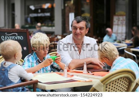 Family, a father with three children, two teenager twins sons, and little cute baby girl, are having fun in cafe on summer terrace in a center of busy city street, boy playing with gadget smart phone - stock photo