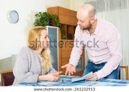 Family a wife and a husband arguing over filling in some documents and financial forms - stock photo