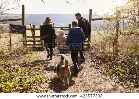 Family and dog walking to gate in the countryside, back view - stock photo