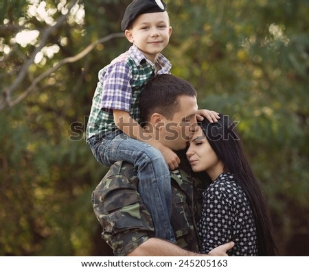 Family and soldier in a military uniform say goodbye before a separation - stock photo