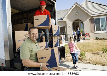 Family and worker unloading delivery van in front of a new house - stock photo
