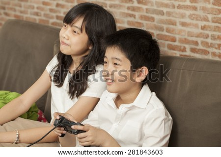family, Asian Thai relatives brother and sister sit on a sofa together playing game - stock photo