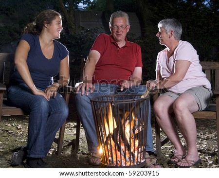 Family at campfire in the garden - stock photo