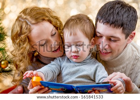 Family at christmas tree. Parents read book to kid. - stock photo