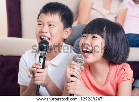Family at home. Portrait of a happy Asian children singing karaoke through microphone in the living room - stock photo