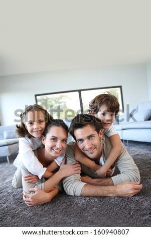 Family at home relaxing on carpet - stock photo