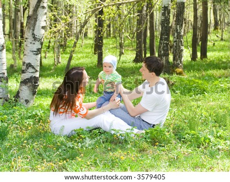 Family at nature. Three persons. Grass. Green forest. - stock photo