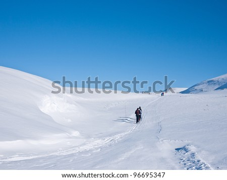Family at ski passing a snow formation in Norwegian mountain at easter - stock photo