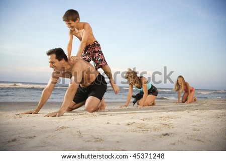 Family at the beach playing leap frog. Horizontal shot. - stock photo