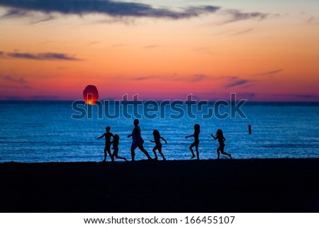 Family at the beach watching a chinese candle lantern, focus on lantern. - stock photo