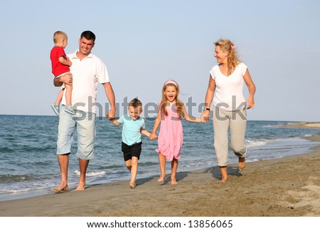 family at the summer holiday, running the beach - stock photo