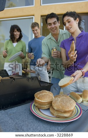 Family BBQ-ing with hamburger buns( burgers in focus family in background) - stock photo