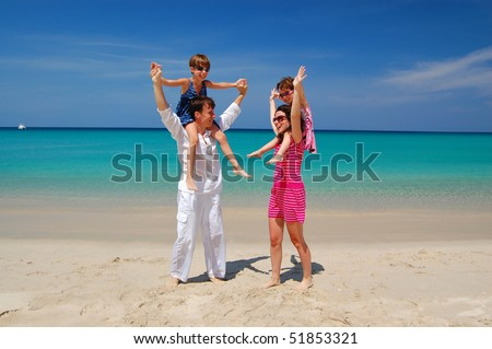Family beach vacation. Daughters sitting on their parents shoulders and having fun - stock photo