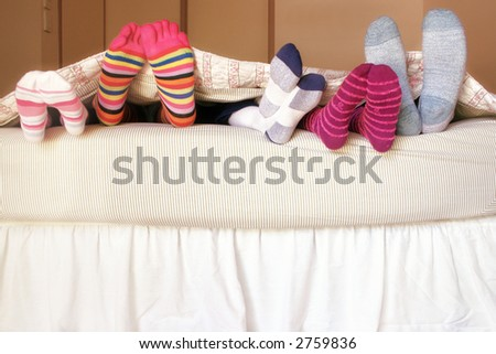 Family Bed:  The kids climb into bed on a weekend morning to snuggle up with mom and dad. - stock photo