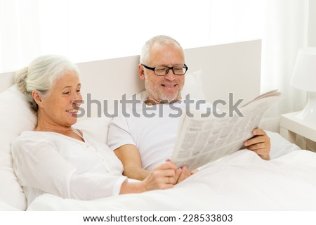 family, bedtime, resting, age and people concept - happy senior coupler with newspaper lying in bad at home - stock photo