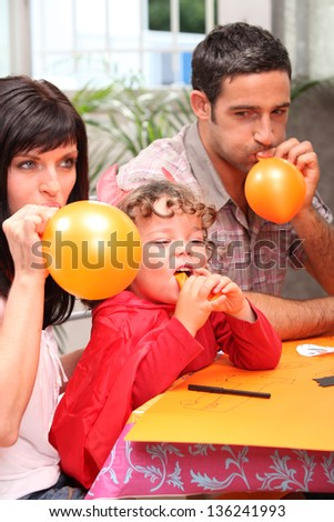 Family blowing balloons for a party - stock photo