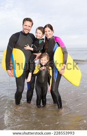 Family Bodyboarding on the Beach - stock photo