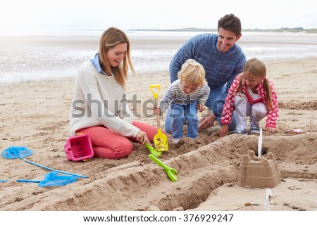 Family Building Sandcastles On Beach Together - stock photo