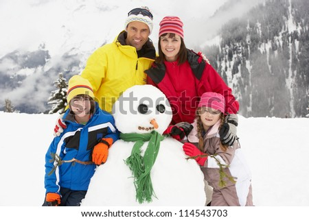 Family Building Snowman On Ski Holiday In Mountains - stock photo