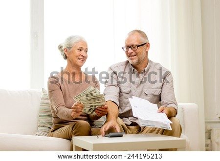 family, business, savings, age and people concept - smiling senior couple with papers, money and calculator at home - stock photo