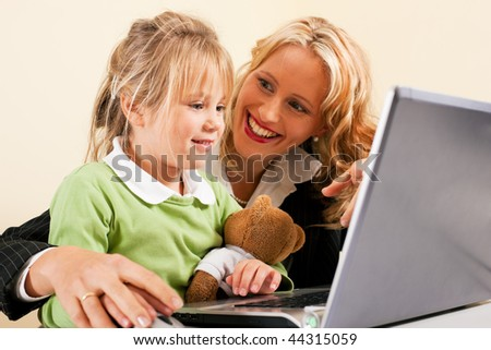 Family Business - telecommuter Businesswoman and mother showing her little daughter how these computer and internet things work - stock photo